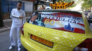 Uljan Kolgjegja, 37, an Albanian taxi driver, points to a picture of U.S. Republican candidate Donald Trump in his car in the Albanian capital, Tirana, on Sept. 26, 2016. (Hektor Pustina / AP)