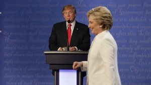 Republican presidential nominee Donald Trump waits behind his podium as Democratic presidential nominee Hillary Clinton makes her way off the stage following the third presidential debate at UNLV in Las Vegas on Wednesday, Oct. 19, 2016. (AP / David Goldman)