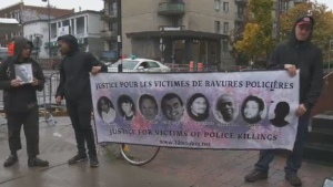 Protesters hold a banner featuring the pictures of several people who died due to alleged excessive force on the part of Quebec police.