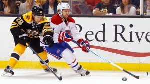 Montreal Canadiens' David Desharnais tries to get around Boston Bruins defenseman John-Michael Liles (26) during the third period of the Montreal Canadiens 4-2 win over the Boston Bruins in an NHL hockey game in Boston on Saturday, Oct. 22, 2016. (AP Photo/Winslow Townson)