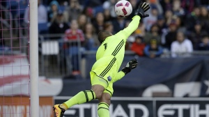 Montreal Impact goalkeeper Evan Bush is unable to stop a ball kicked by New England Revolution forward Diego Fagundez. (AP Photo/Steven Senne)