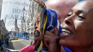 Rita Jeptoo of Kenya poses with her trophy at the finish line of the 2013 Boston Marathon, on April 15, 2013. (Elise Amendola / AP)