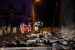Rescuers stand by rubble in the village of Visso, central Italy, Wednesday, Oct. 26, 2016 following an earthquake. A pair of powerful aftershocks shook central Italy on Wednesday, knocking out power, closing a major highway and sending panicked residents into the rain-drenched streets just two months after a powerful earthquake killed nearly 300 people. (Matteo Crocchioni/ANSA via AP)