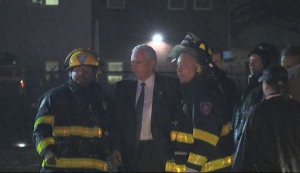 Republican presidential candidate Indiana Gov. Mike Pence talks with firefighters at New York's LaGuardia Airport after his campaign plane slide off the runway while landing on Thursday, Oct. 27, 2016. (TV Network Pool via AP)