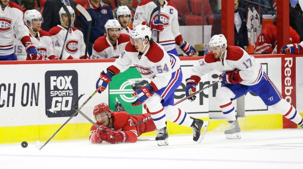 Carolina Hurricanes' Brett Pesce (22) falls to the ice while chasing the puck with Montreal Canadiens' Charles Hudon (54) and Torrey Mitchell (17) (AP Photo/Gerry Broome)