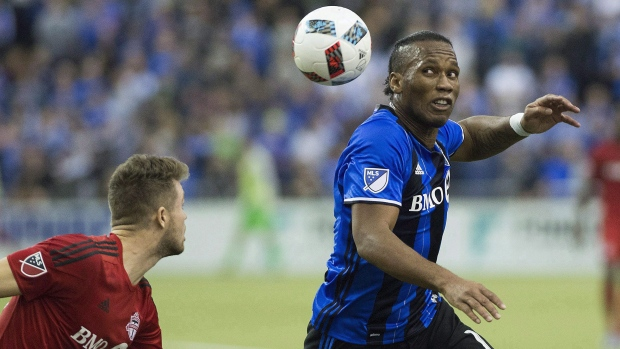 Montreal Impact's Didier Drogba, right, challenges Toronto FC's Eriq Zavaleta during second half soccer action of the first leg of the MLS eastern conference final at the Olympic Stadium in Montreal on November 22, 2016. (Graham Hughes/The Canadian Press)