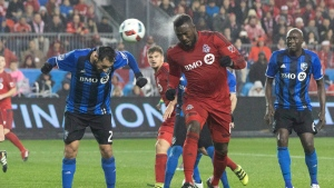 Toronto FC forward Jozy Altidore heads in his team's second goal in front of Montreal Impact forward Matteo Mancosu on Wednesday November 30, 2016. THE CANADIAN PRESS/Chris Young