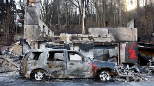 A burnt vehicle sits on a wildfire damaged property in Gatlinburg, Tenn., Friday, Dec. 2, 2016, after residents were allowed back in following the devastating fires on Monday night, Nov. 28. (Michael Patrick/Knoxville News Sentinel via AP)