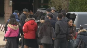 Young people gather in front of the funeral for Darius Brown.
