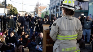 Oakland Battalion Chief Melinda Drayton addresses the media at the scene of a warehouse fire, Sunday, Dec. 4, 2016, in Oakland, Calif. Officials said they are continuing to search the charred debris from the fatal fire that ripped through a late-night dance party in the converted warehouse earlier in the weekend. (AP Photo/Marcio Jose Sanchez)