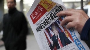 A man reads a newspaper with the headline that reads 'U.S. President-elect Donald Trump delivers a mighty shock to America' at a newsstand in Beijing on Nov. 10, 2016. (AP / Andy Wong)