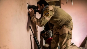 Iraqi soldiers from the 9th division looks through a sniper hole at the Al-Intisar district in Mosul, Iraq, Monday, Dec. 5, 2016. Mosul, Iraq's second-largest city, is the last major Islamic State extremist urban bastion in the country. Iraqi troops have advanced cautiously to avoid civilian casualties. (AP Photo/Manu Brabo