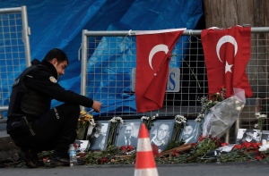 A police officer looks a photographs of the victims displayed a day after an attack at a popular nightclub in Istanbul, Monday, Jan. 2, 2017. (AP Photo/Halit Onur Sandal)