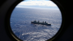 FILE - In this March 31, 2014 file photo, HMAS Success scans the southern Indian Ocean, near the coast of Western Australia, as a Royal New Zealand Air Force P3 Orion flies over, while searching for missing Malaysia Airlines Flight MH370. After nearly three years, the hunt for Malaysia Airlines Flight 370 ended in futility and frustration on Tuesday, Jan. 17, 2017, as crews completed their deep-sea search of a desolate stretch of the Indian Ocean without finding a single trace of the plane. (AP Photo/Rob Griffith, File)
