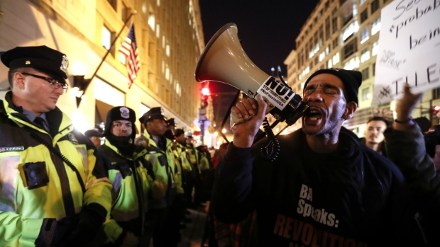 Protesters stand against a line of police guarding the front of the National Press Building ahead of the presidential inauguration in Washington on Thursday, Jan. 19, 2017. (AP / John Minchillo)