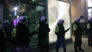 Montreal police officers wearing protective gear stand in front of Station 20, where protesters smashed a window during an anti-Trump march on Jan. 20, 2017 (CTV Montreal/Denise Roberts)