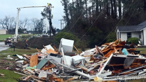 "The remains of a house sit in a debris pile along Highway 122 as power line workers repair a downed line Sunday, Jan. 22, 2017, near Barney, Ga. The National Weather Service said Sunday that southern Georgia, northern Florida and the corner of southeastern Alabama could face ""intense and long track"" tornadoes, scattered damaging winds and large hail. (AP Photo/Phil Sears)"