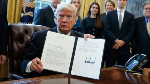 U.S. President Donald Trump shows his signature on an executive order on the Keystone XL pipeline, Tuesday, Jan. 24, 2017, in the Oval Office of the White House in Washington. (AP Photo/Evan Vucci)