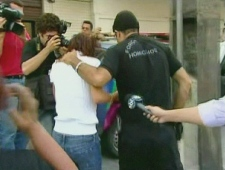 In this image taken from video, Amanda Rodrigues, in white, the wife of Arturo Gatti, is seen being taken into custody by Brazilian police on Sunday, July 12, 2009.