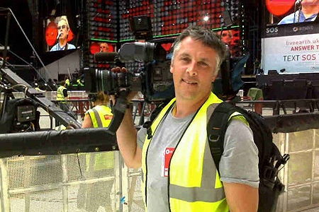 Cameraman Hugh Haugland working at an outdoor concert.