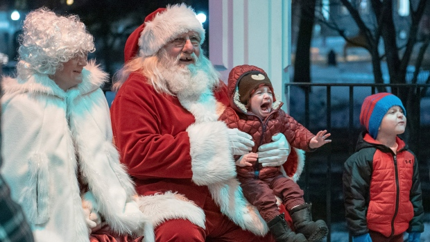 A child cries while taking a photo with Santa