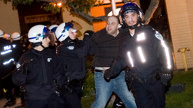 Police arrest a protester during a large demonstration designed as an act of defiance against a legal crackdown by the Quebec government, in Montreal, Friday, May 18, 2012. THE CANADIAN PRESS/Graham Hughes