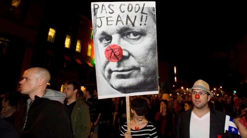 A protester holds a sign depicting Premier Jean Charest during a large rally designed as an act of defiance against a legal crackdown by the Quebec government, in Montreal, Friday, May 18, 2012. THE CANADIAN PRESS/Graham Hughes