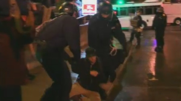 A man drops to his knees as police arrest him for protesting in Quebec City (May 28, 2012)