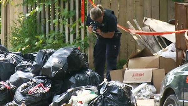 A police officer photographs the where the human torso was found in ontreal. According to reports, the victim is 33-year-old Lin Jun from Wuhan, China.
