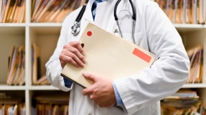 Undated stock image of doctor holding files.