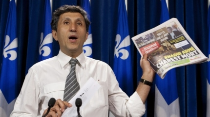 Quebec Solidaire leader Amir Khadir holds a copy of local newspaper displaying a picture of a mocked famous painting showing a dead Jean Charest and Amir Khadir holding a firearm, Tuesday, June 12, 2012 at the legislature in Quebec City. The mocked painting had been seized at his house when his daughter Yalda was arrested by Montreal police. THE CANADIAN PRESS/Jacques Boissinot