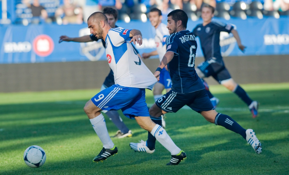 Sporting Kansas City's Paulo Nagamura pulls the shirt of Montreal Impact's Marco Di Vaio during first half MLS soccer action in Montreal, Wednesday, July 4, 2012. THE CANADIAN PRESS/Graham Hughes