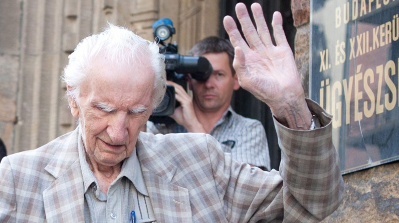 Alleged Hungarian war criminal Laszlo Csatary, right, waves and is helped by a relative as he leaves the Budapest Prosecutor's Office after he was questioned by detectives on charges of war crimes during WWII and prosecutors ordered his house arrest in Budapest, Hungary, Wednesday, July 18, 2012.  (AP / MTI, Bea Kallos)