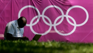 A man uses his computer against a backdrop of Olympic rings in London's St. James Park Monday, July 23, 2012. (AP Photo/Charlie Riedel)