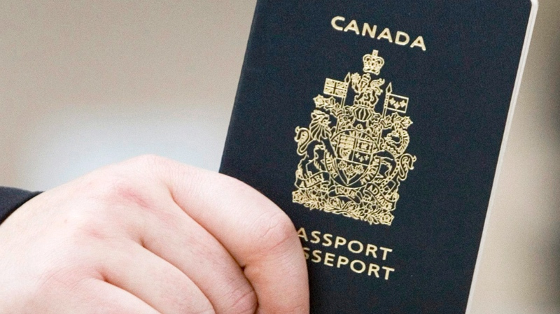 A passenger holds his Canadian passport before boarding a flight in Ottawa, Ont. on Jan 23, 2007. (Tom Hanson / THE CANADIAN PRESS)