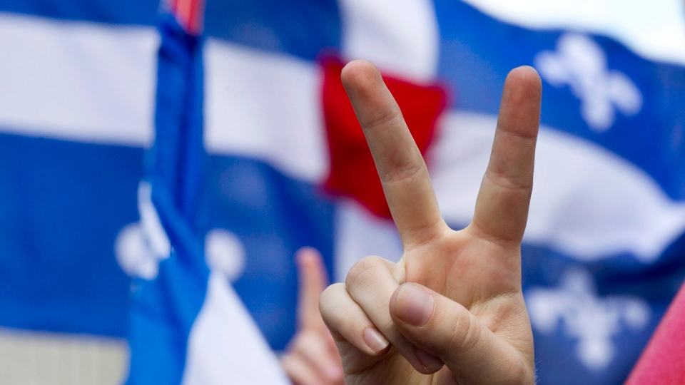 In this June 22, 2012 file photo, a demonstrator gives a peace sign in front of the Quebec flag with the symbolic red square in the middle during a march in the streets of Montreal. (Paul Chiasson / The Canadian Press)