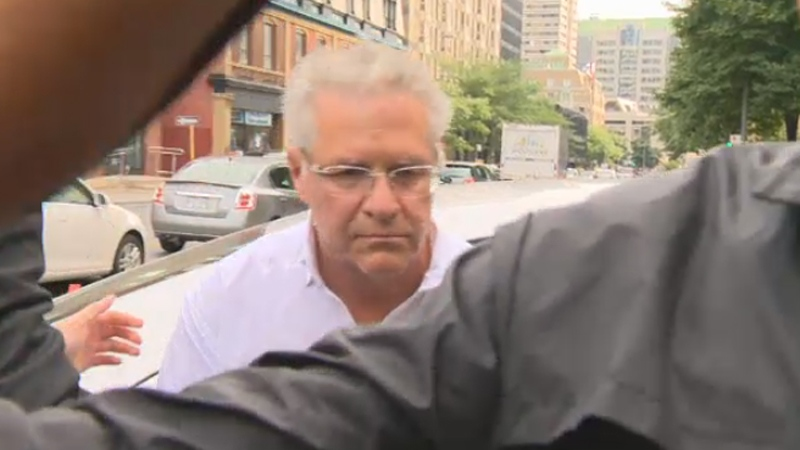 Shielded by police officers, Tony Accurso steps out of a car after being arrested. He is one of four people facing six counts each of fraud, conspiracy, forgery and breach of trust by a public officer. (Aug. 9, 2012)
