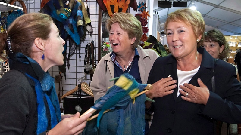 Parti Quebecois Leader Pauline Marois,right, gestures as she visits an artists exhibition with candidate Agnes Maltais, centre, in Quebec City Friday, August 10, 2012. Quebecers are going to the polls on Sept. 4. THE CANADIAN PRESS/Clement Allard