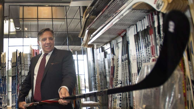 Coalition Avenir Quebec leader Francois Legault checks out a hockey stick during a visit to a sports