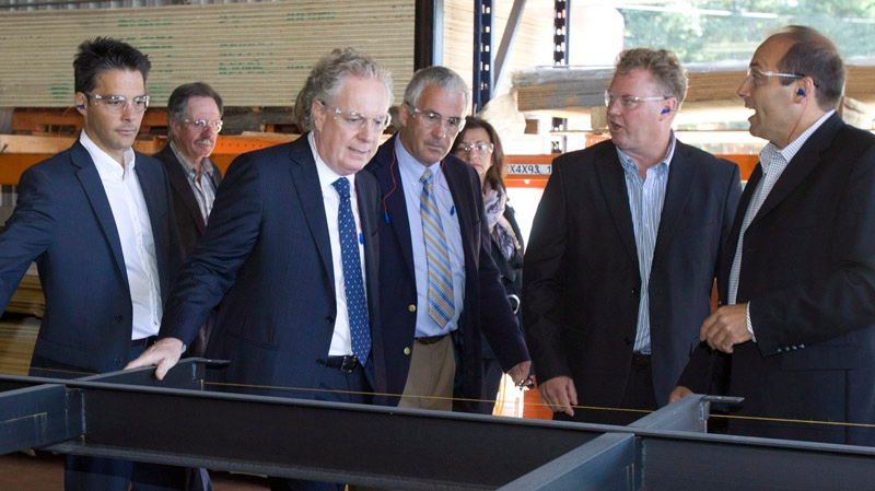 Quebec Liberal Party Leader Jean Charest , centre left, visits a shop where they build portable structures in Saint-Romain, Que., on Wednesday, August 29, 2012. Quebecers are going to the polls on Sept. 4. THE CANADIAN PRESS/Jacques Boissinot