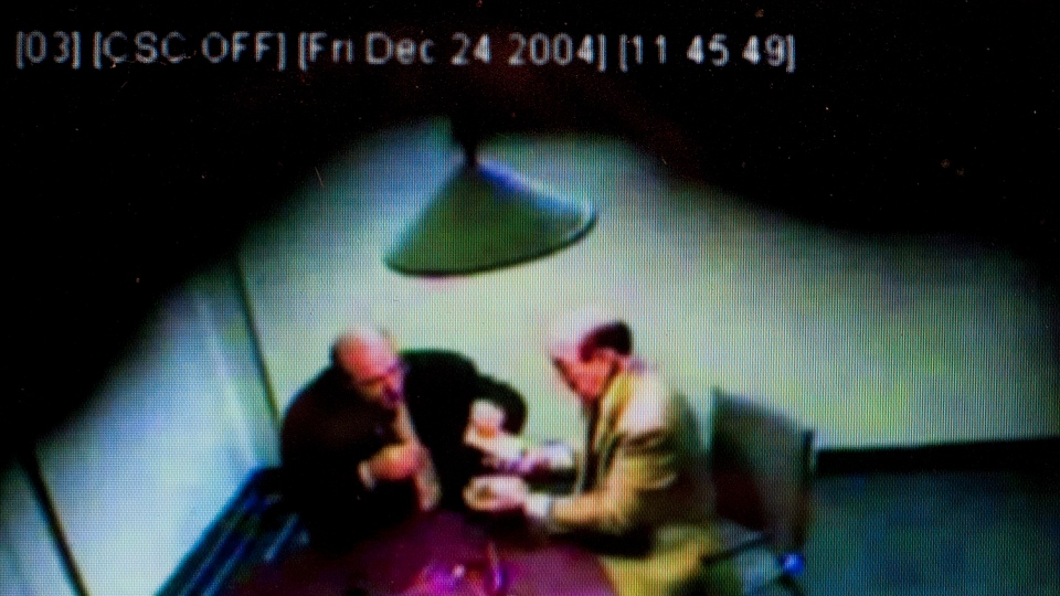 A photo taken in Montreal, Wednesday, Sept. 26, 2012, from an RCMP surveillance video presented as evidence at the Charbonneau commission, an inquiry looking into corruption and collusion in Quebec's construction industry, allegedly shows Nick Rizzuto Sr., right, exchanging tens of thousands of dollars with Nicolo Milioto, left, former head of Mivela Construction Inc. (Graham Hughes / THE CANADIAN PRESS)